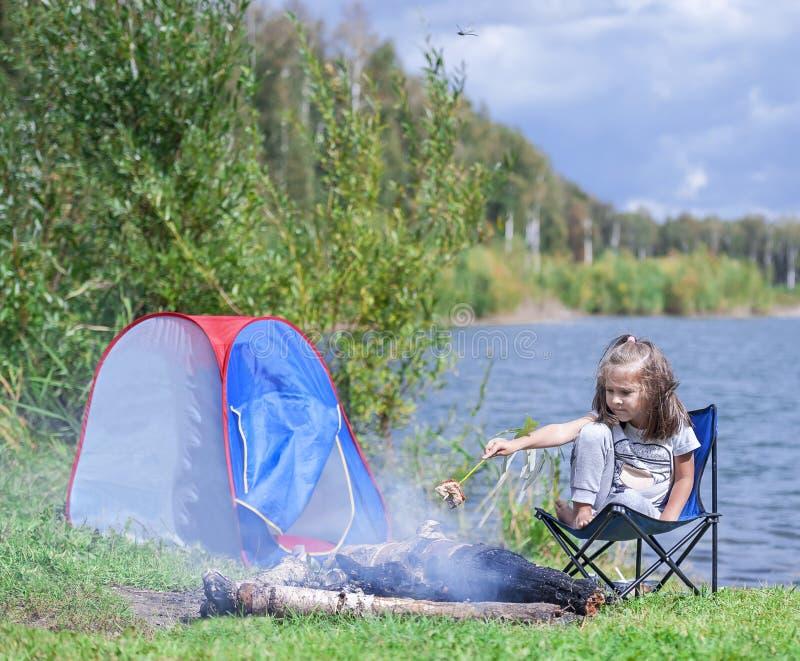 Petite fille s'asseyant près du feu de camp Pain de torréfaction de fille au-dessus de feu de camp photo libre de droits