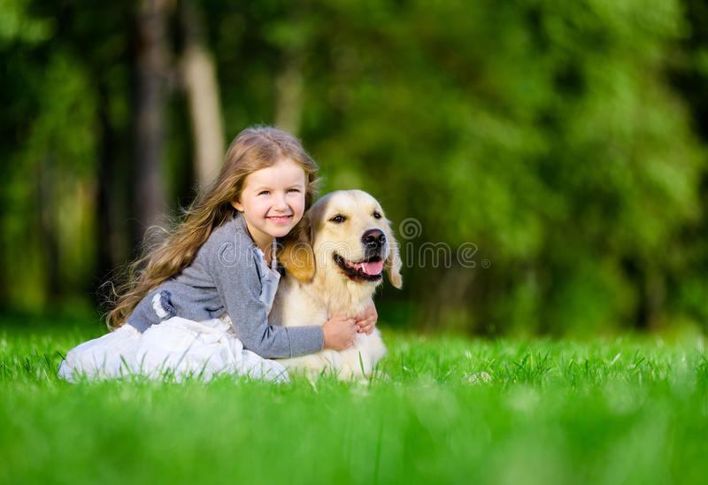 Petite fille s'asseyant sur l'herbe avec le golden retriever image stock