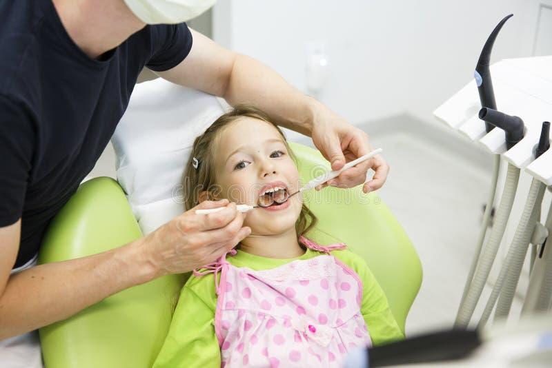 Petite fille s'asseyant sur la chaise dentaire photographie stock