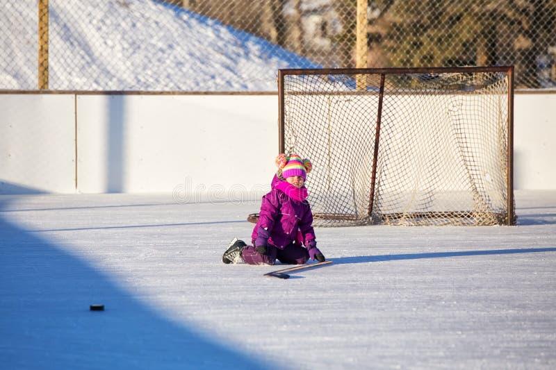 Petite fille s'asseyant sur la glace à la piste extérieure photographie stock libre de droits