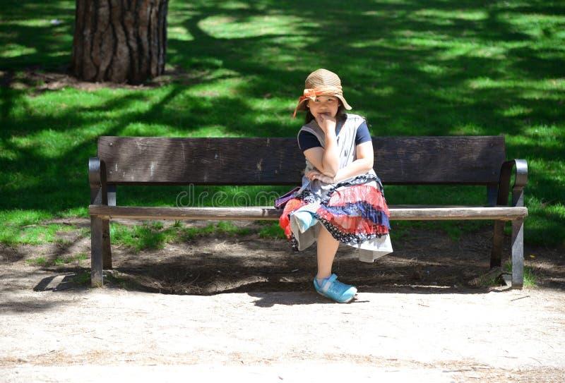 Petite fille s'asseyant sur le banc en parc photographie stock
