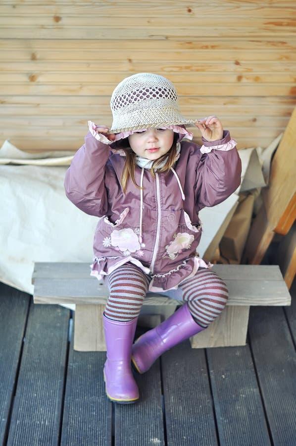 Petite fille s'asseyant sur le banc sur la terrasse de la maison en bois dans la campagne avec un chapeau de paille photos stock