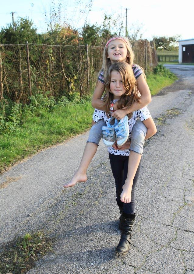 Petite fille s'asseyant sur le dos de girlsphotos libres de droits
