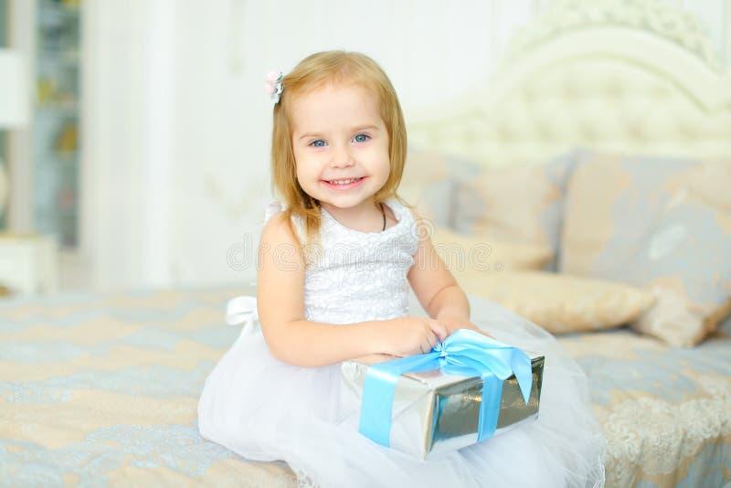 Petite fille s'asseyant sur le lit avec le présent et la robe blanche de port photos libres de droits