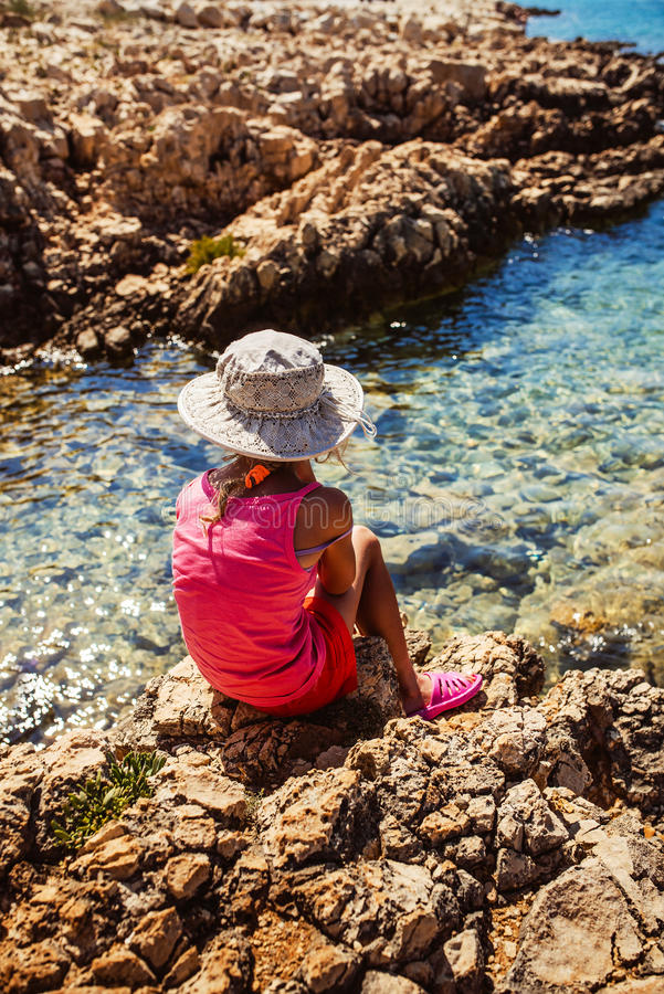 Petite fille s'asseyant sur le rivage rocheux de la mer photographie stock libre de droits