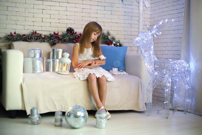Petite fille s'asseyant sur le sofa avec des cadeaux de Noël images libres de droits