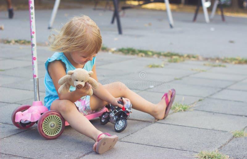 Petite fille s'asseyant sur son scooter, jouant avec des jouets images stock