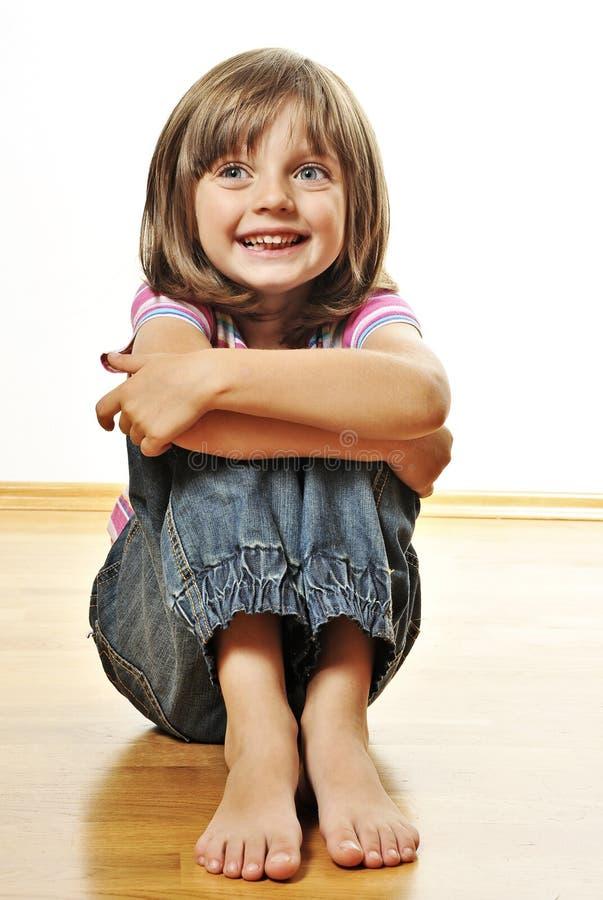 Petite fille s'asseyant sur un étage images libres de droits