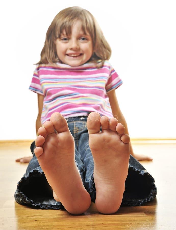 Petite fille s'asseyant sur un étage en bois photographie stock libre de droits