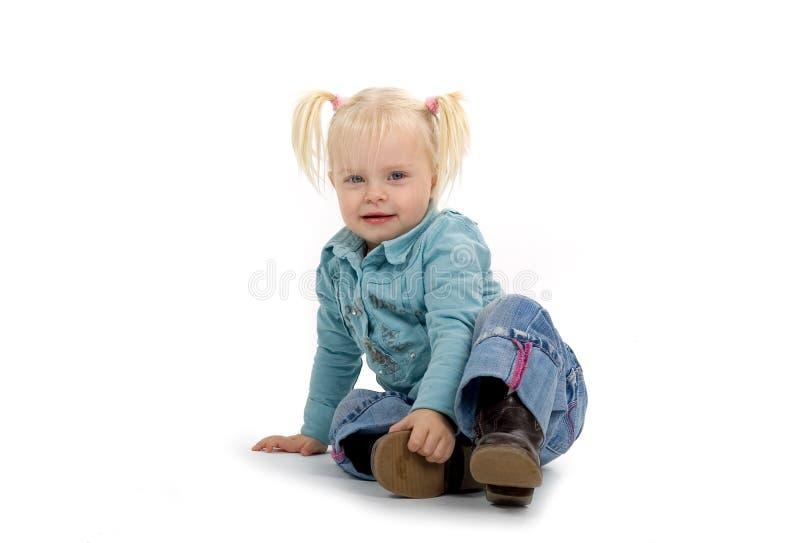 Petite fille s'asseyante photographie stock