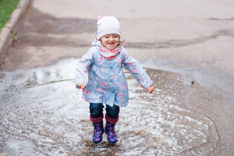 Petite fille sautant dans le magma photographie stock