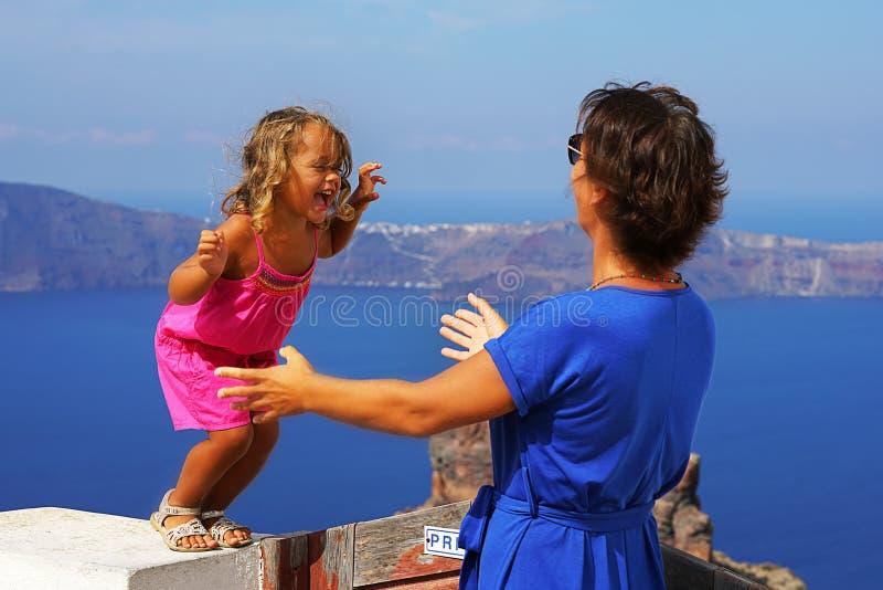 petite fille sautant dans les bras de la maman contre la vue gentille de Santorini photo libre de droits