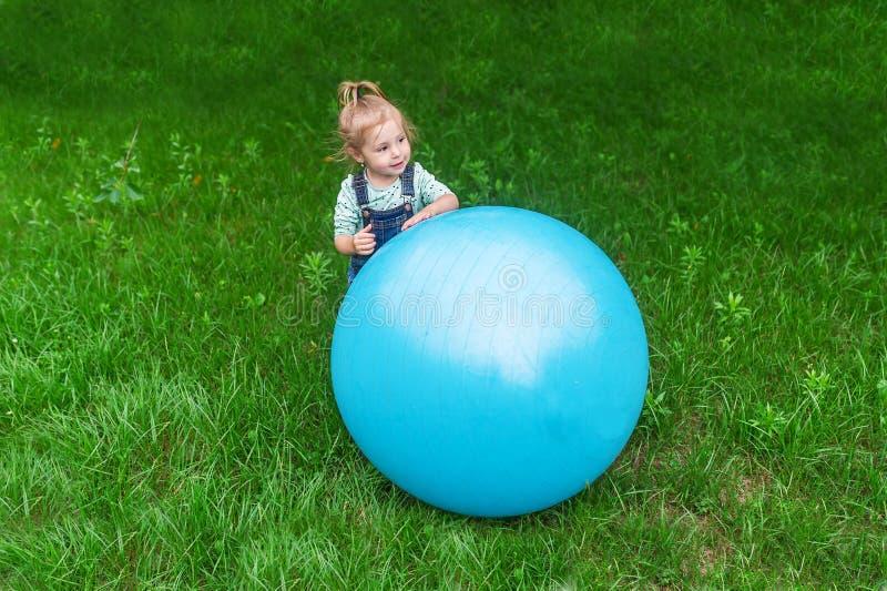 Petite fille sautant sur la boule gonflable bleue sur la pelouse photo stock