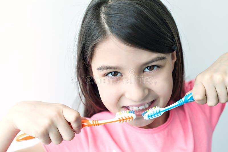 Petite fille se brossant les dents photo stock