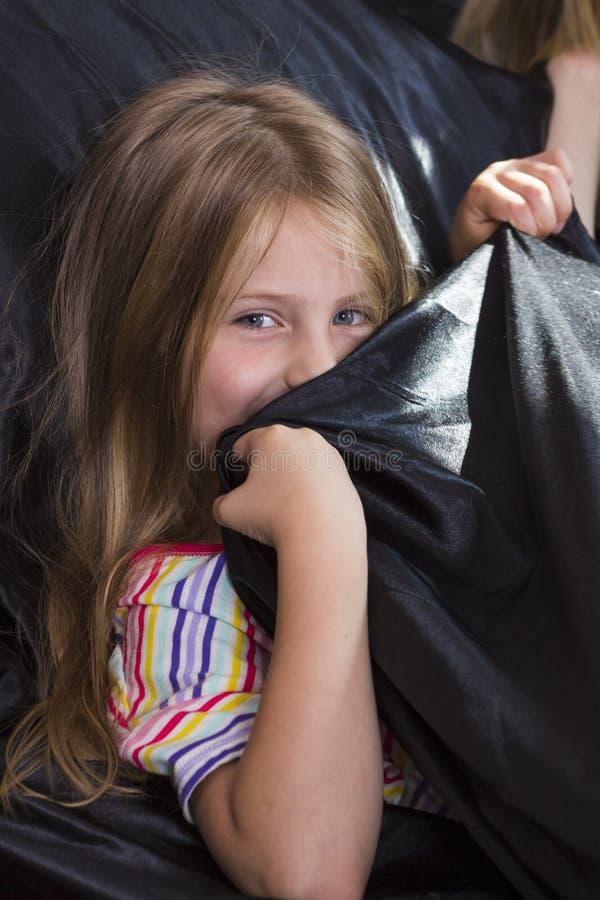 Petite fille se situant dans le lit à la maison image libre de droits