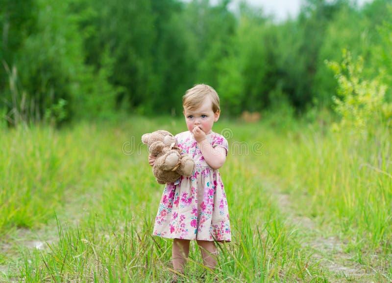 Petite fille se tenant dans l'herbe tenant le grand ours de nounours image stock