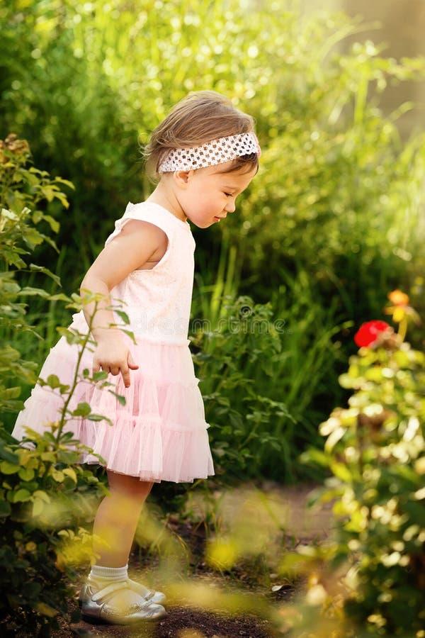 Petite fille se tenant dans un jardin image stock