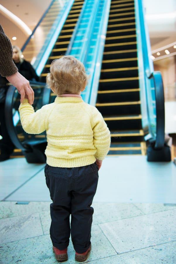 Petite fille se tenant devant l'escalator images libres de droits