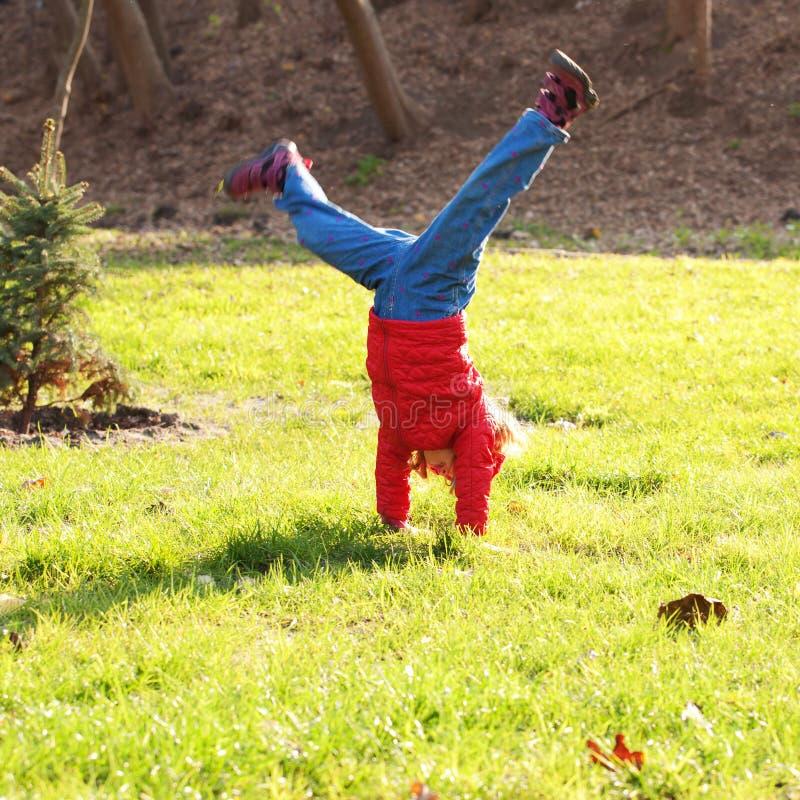 Petite fille se tenant sur des mains à l'envers photo libre de droits
