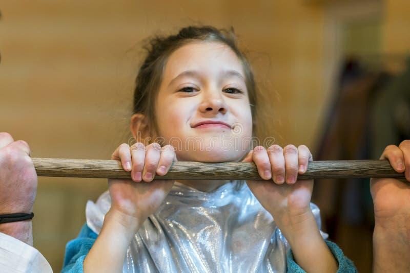 Petite fille se tirant sur une barre transversale en bois photographie stock