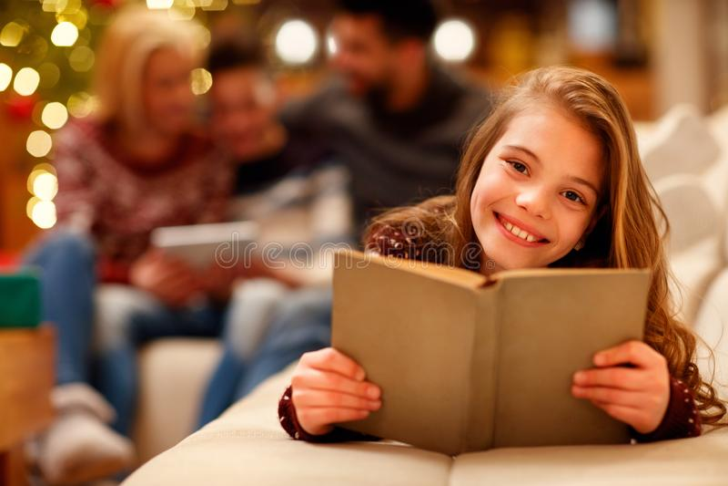 Petite fille se trouvant et lisant le livre d'enfants pour Noël photo libre de droits
