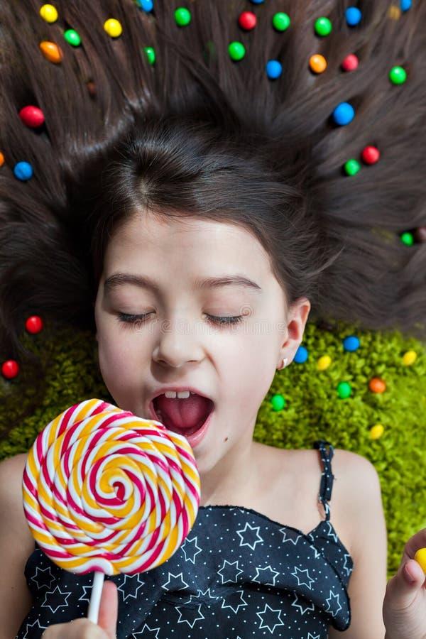 Petite fille se trouvant sur le plancher avec ses yeux fermés et mangeant la sucrerie photo libre de droits