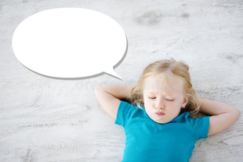 Petite fille se trouvant sur le plancher en bois blanc avec une bulle de la parole au-dessus de sa tête image stock