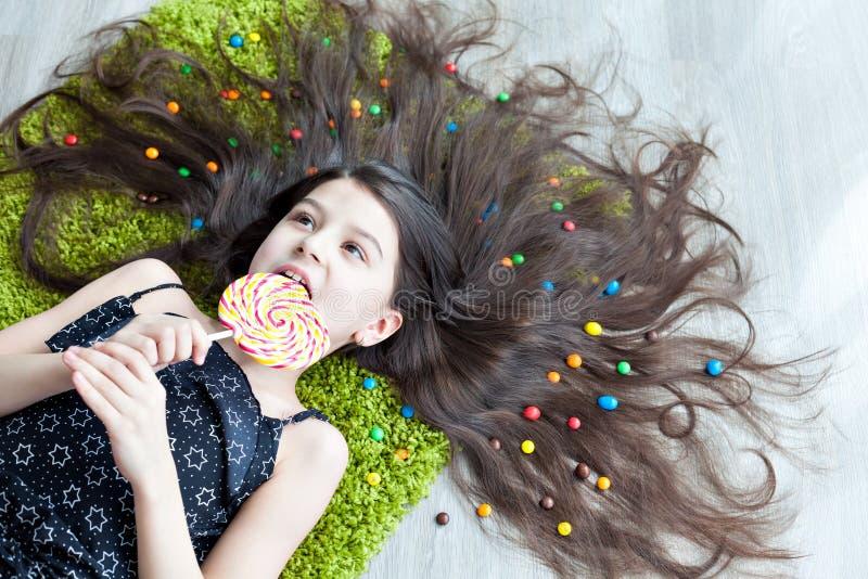 Petite fille se trouvant sur le plancher et mangeant la sucrerie image stock