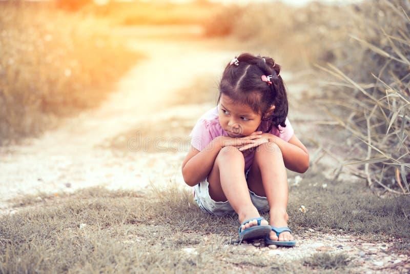 Petite fille seule et triste s'asseyant en parc image libre de droits