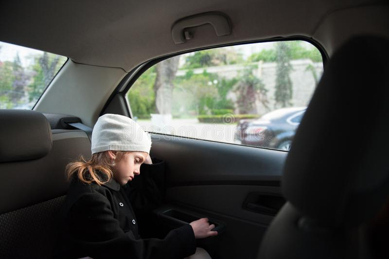 Petite fille seule triste dans le chapeau et le manteau de laine se reposant à l'intérieur de la voiture près de la fenêtre photos libres de droits