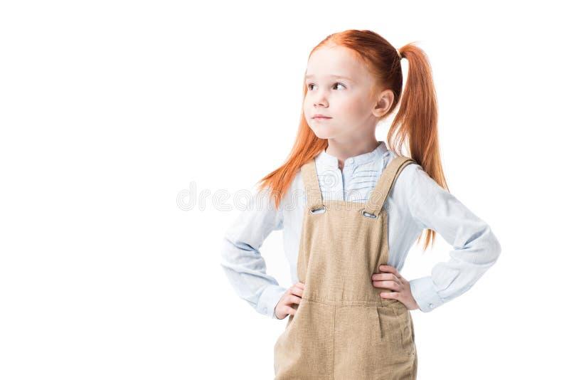 Petite fille songeuse se tenant avec des mains sur la taille et regardant loin photographie stock