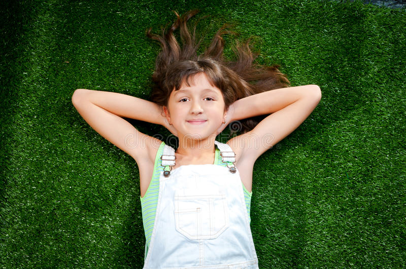 Petite fille souriant sur l'herbe photo stock