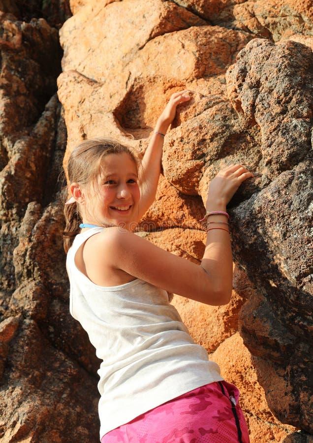 Petite fille souriante alors qu'elle gravit le rocher rouge de la montagne photographie stock