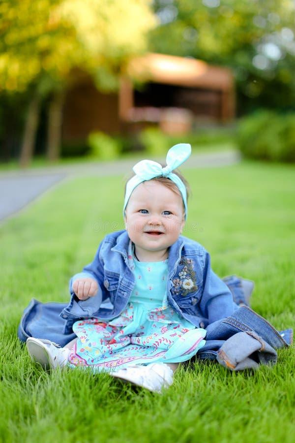 Petite fille souriante assise sur une herbe verte et portant une veste de jeans image stock