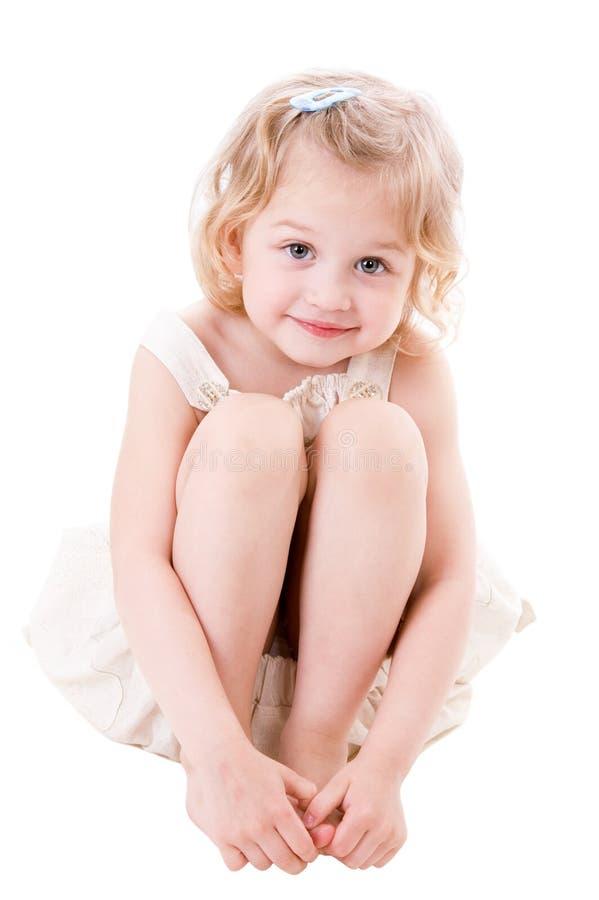 Petite fille souriante s'asseyant sur le blanc images stock