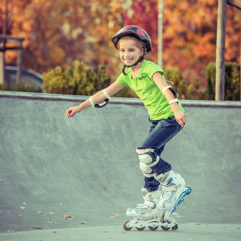 Petite fille sur des patins de rouleau photographie stock libre de droits