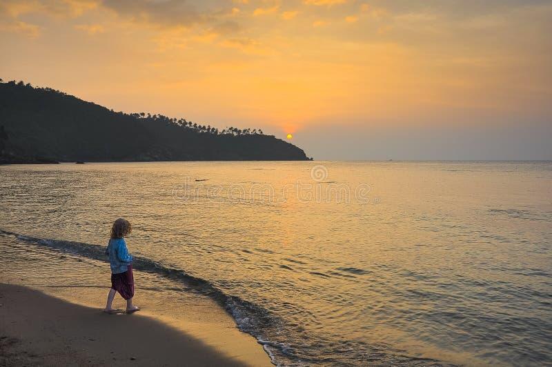 Petite fille sur la plage au fond de coucher du soleil images libres de droits