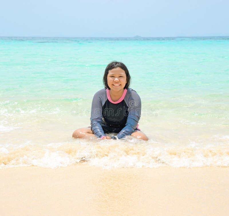 Petite fille sur la plage avec la mer bleue photos libres de droits