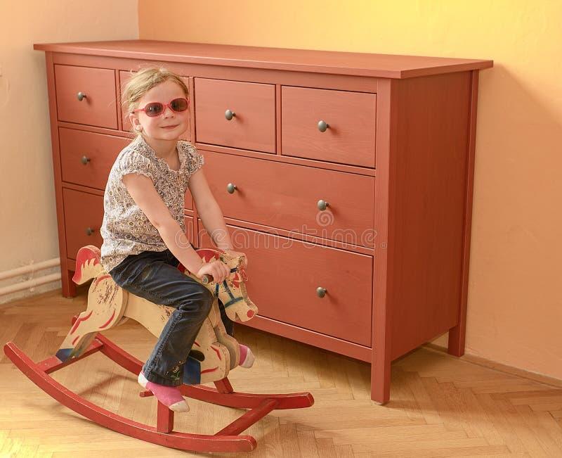 Petite fille sur le cheval d'oscillation La petite fille porte les lunettes rouges image libre de droits