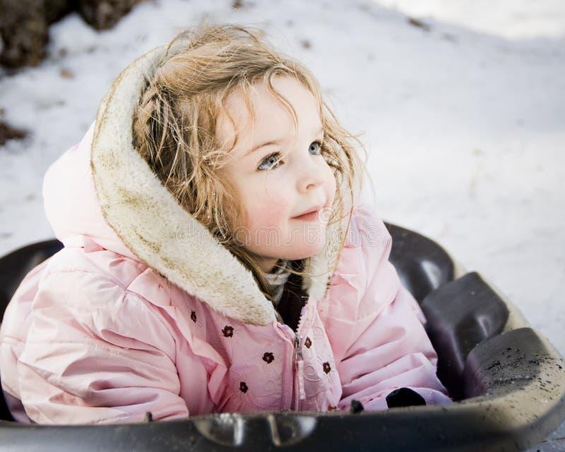 Petite fille sur le traîneau de neige photos libres de droits