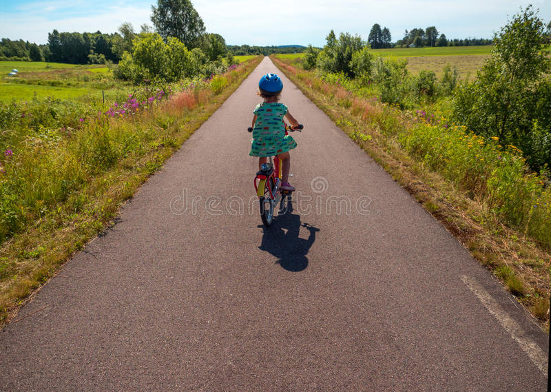 Petite fille sur le vélo dans le paysage suédois photographie stock libre de droits