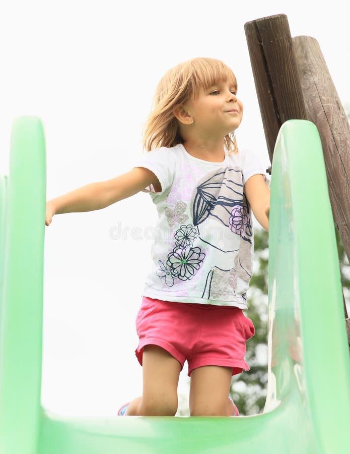Petite fille sur une glissière photo stock