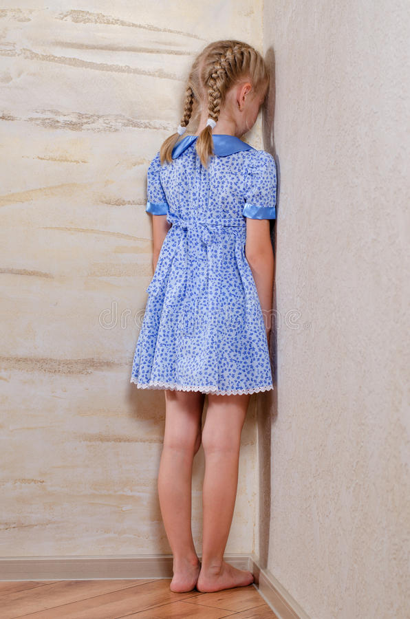 Petite fille tenant dans le revêtement faisant le coin le mur images libres de droits
