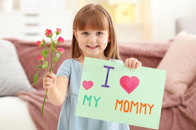 Petite fille tenant la carte de voeux et la fleur pour le jour du ` s de mère images stock