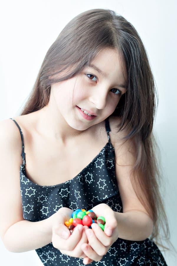 Petite fille tenant la sucrerie dans les mains photos stock