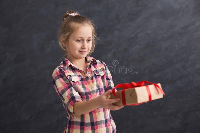 Petite fille tenant le boîte-cadeau sur le fond foncé photographie stock libre de droits