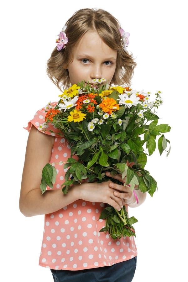 Petite fille tenant le groupe de wildflowers photos stock