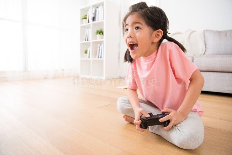 Petite fille tenant le jeu vidéo heureux de jeu de manette photographie stock