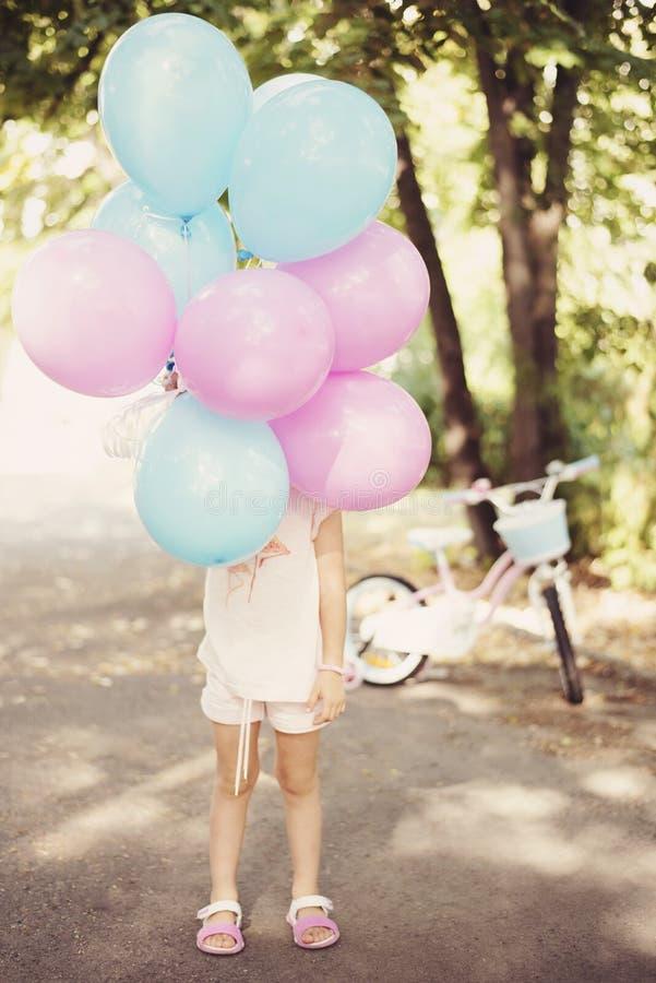 Petite fille tenant les ballons colorés dans le rose et le bleu Bicyclette à l'arrière-plan - cadeau d'anniversaire Fille d'anniv photographie stock libre de droits