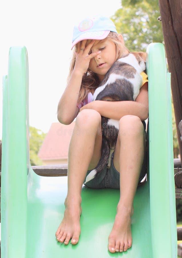 Petite fille tenant sa tête et un chiot sur une glissière photographie stock